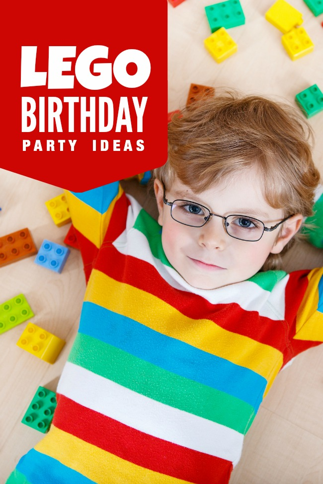 Little blond kid boy playing with lots of colorful plastic blocks indoor. child wearing colorful shirt and glasses having fun with building and creating.